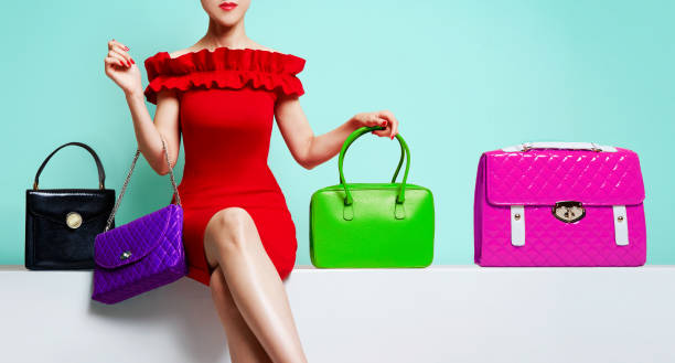 woman with red dress sitting with many colourful purses. - borsetta foto e immagini stock