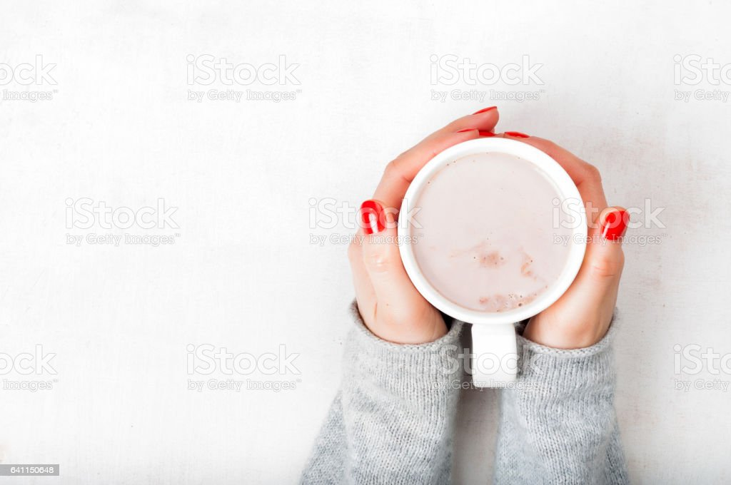 Woman with red fingernaild holding cup of hot cacao beverage on white wooden background stock photo