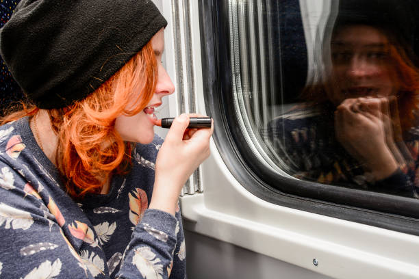 Woman with red hair doing makeup in a train stock photo