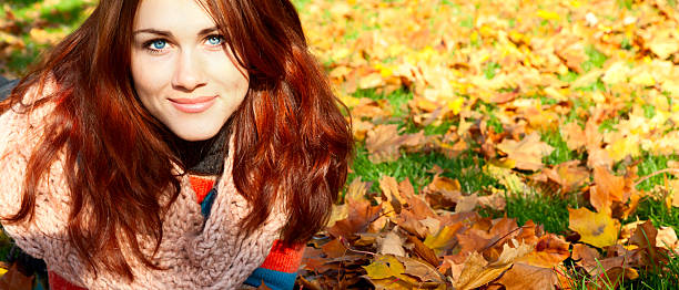 Woman with red hair laying on autumn leaves. stock photo