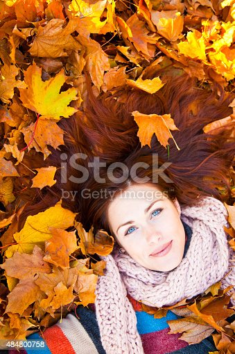 Woman with red hair laying on autumn leaves. She has  a multicolored sweater.
