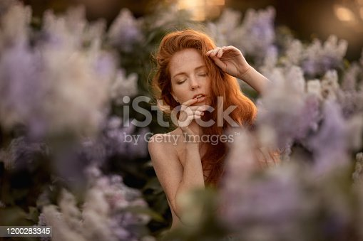 1054970060 istock photo A woman with red hair long and curly in a Bush with purple flowers 1200283345