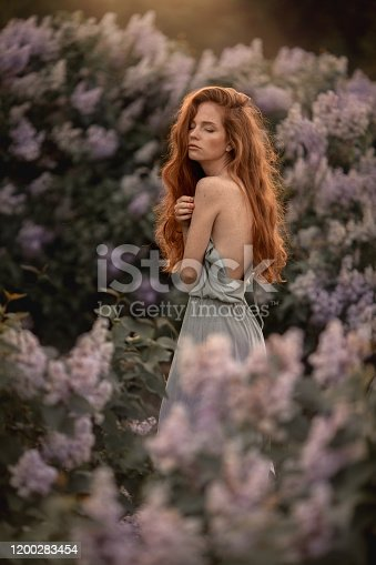 1054970060 istock photo A woman with red hair long and curly in a Bush with purple flowers 1200283454