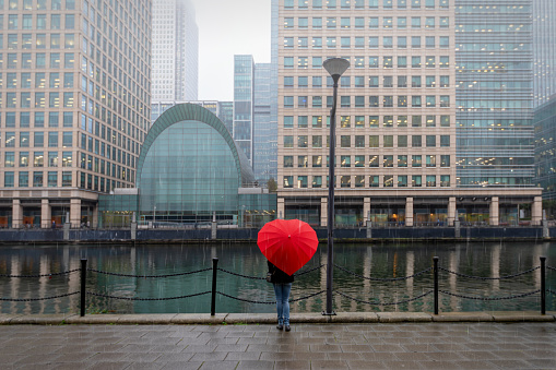 Woman with red, heart shaped umbrella stands in London Canary Wharf
