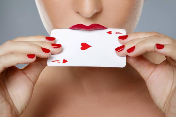 frau mit roten lippen ist ass-karte in den händen halten. - bester nagellack stock-fotos und bilder