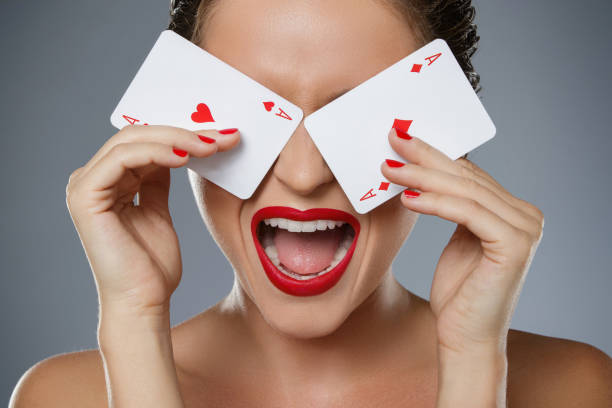 frau mit roten lippen hält zwei asse in der hand - bester nagellack stock-fotos und bilder