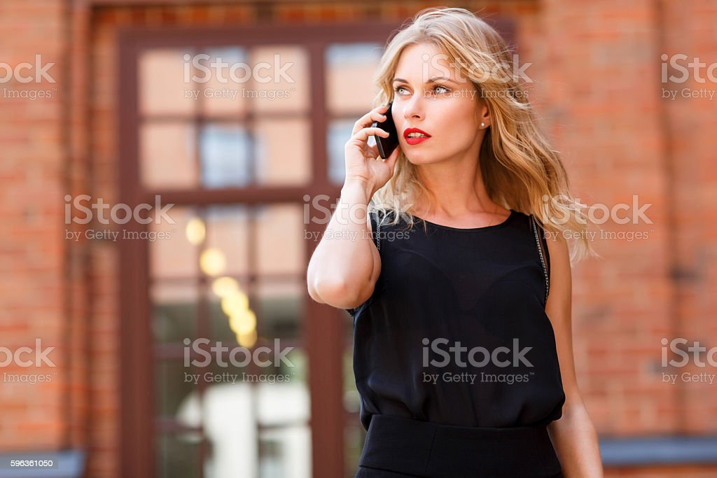 Woman with red lipstick and black blouse talking on cellphone royalty-free stock photo