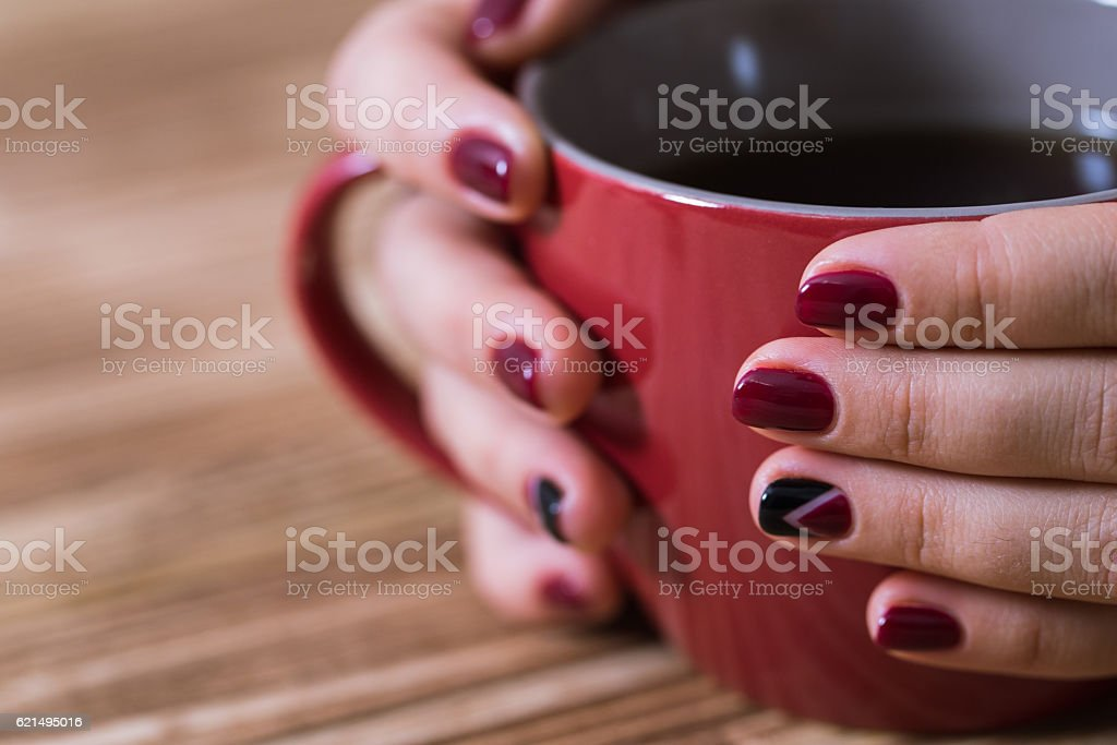 Woman with red manicure holding a red cup of tea photo libre de droits