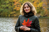 Woman with a red maple leaf on the background of the forest in the autumn afternoon