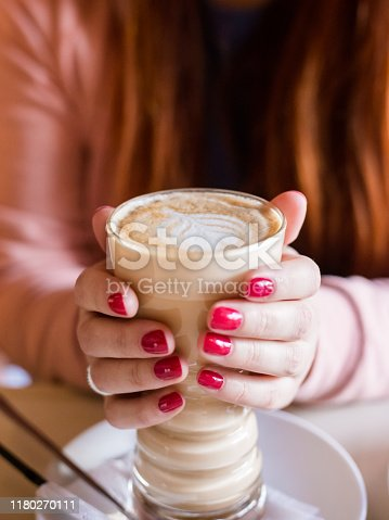 istock Woman with red nails sitting and holding a hot cup of coffee. Closeup of hands with latte, Red manicure 1180270111