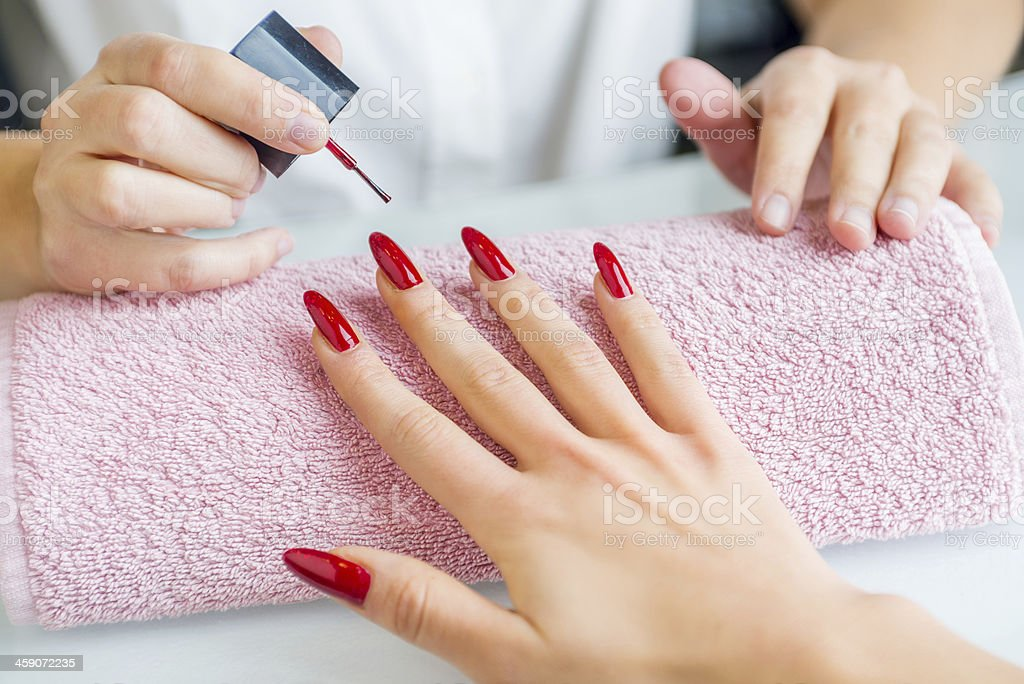 A woman with red painted nails getting a manicure stock photo