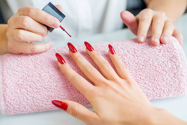 A woman with red painted nails getting a manicure