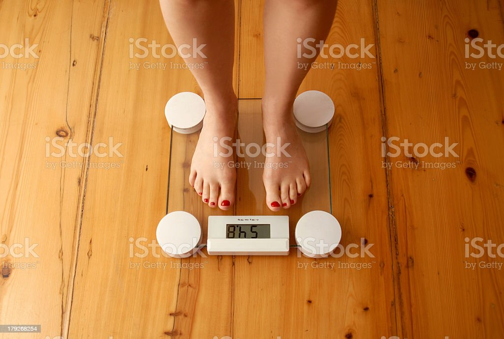 A woman with red painted toe nails standing on a scale  stock photo