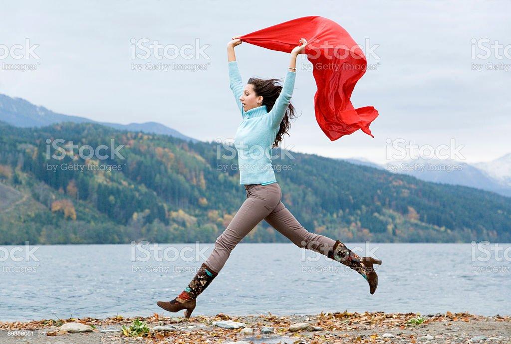 Donna con la sciarpa rossa saltando di gioia nella area di montagna foto stock royalty-free