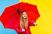 istock Woman with red umbrella having fun in rainy day 1178931998