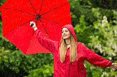 istock Woman with red umbrella having fun in rainy day 1183697017