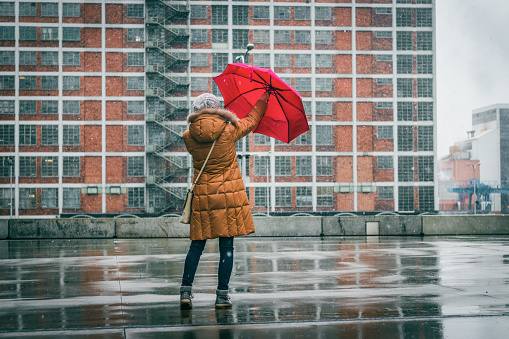 Woman with red umbrella standing in city during snowing.