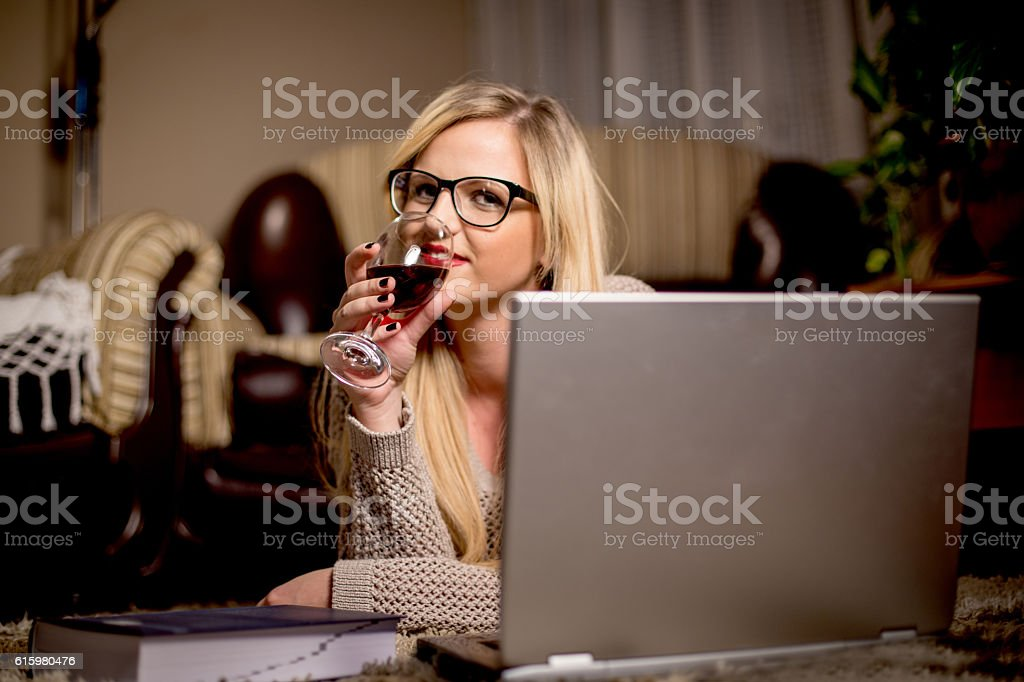 Woman with red wine tablet and laptop at night stock photo