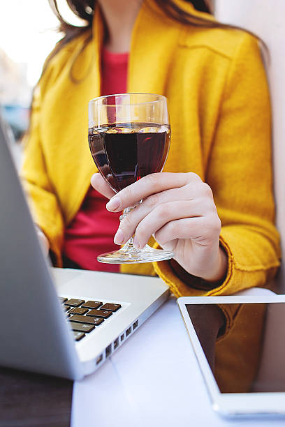 Woman with red wine tablet and laptop in street cafe stock photo