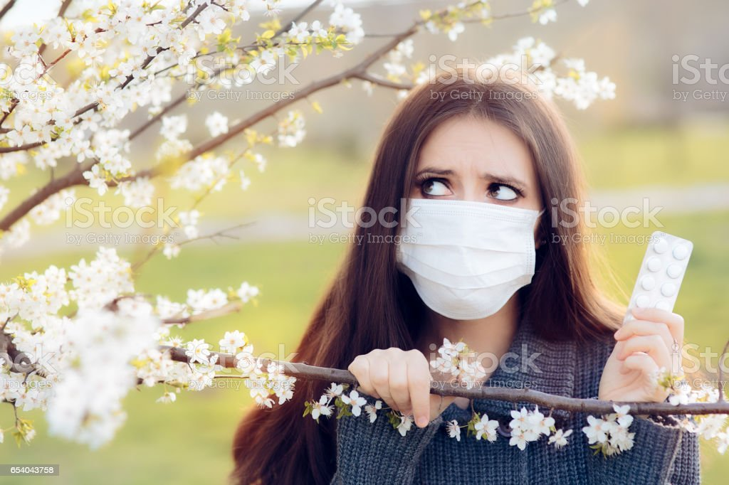 Woman with Respirator Mask Fighting Spring Allergies Outdoor stock photo