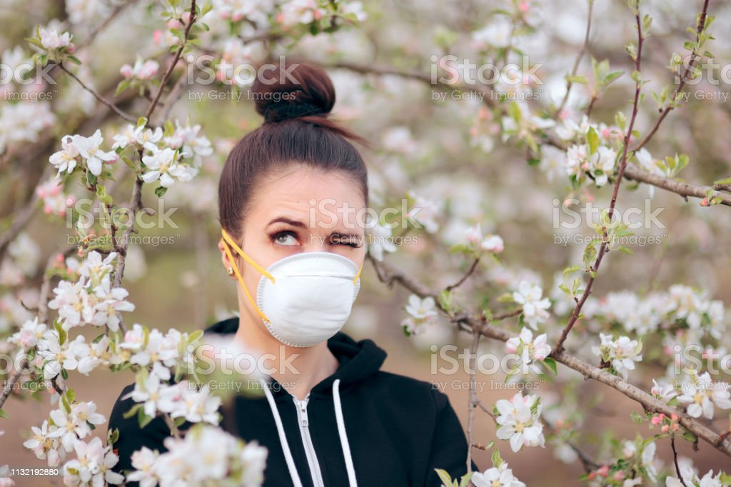 Woman with Respirator Mask Fighting Spring Allergies stock photo