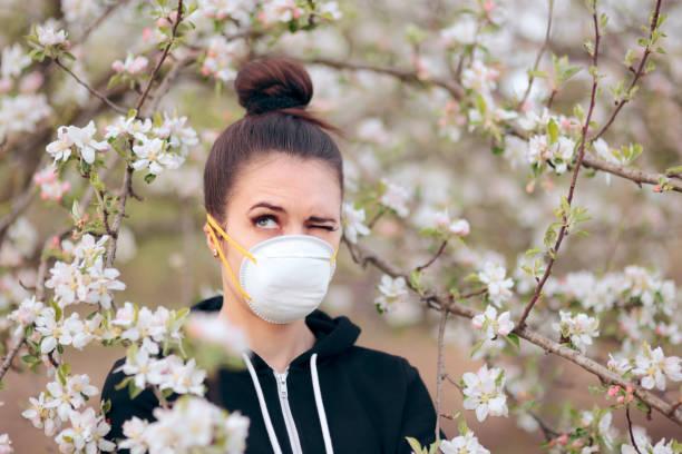 woman with respirator mask fighting spring allergies - pyłek zdjęcia i obrazy z banku zdjęć