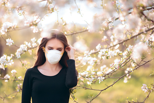 istock Woman with Respirator Mask Fighting Spring Allergies 1132192895