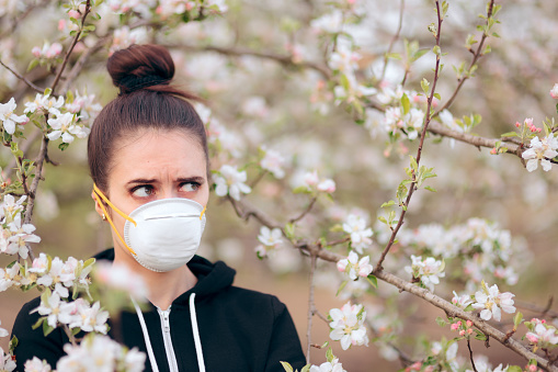 istock Woman with Respirator Mask Fighting Spring Allergies 1132192896