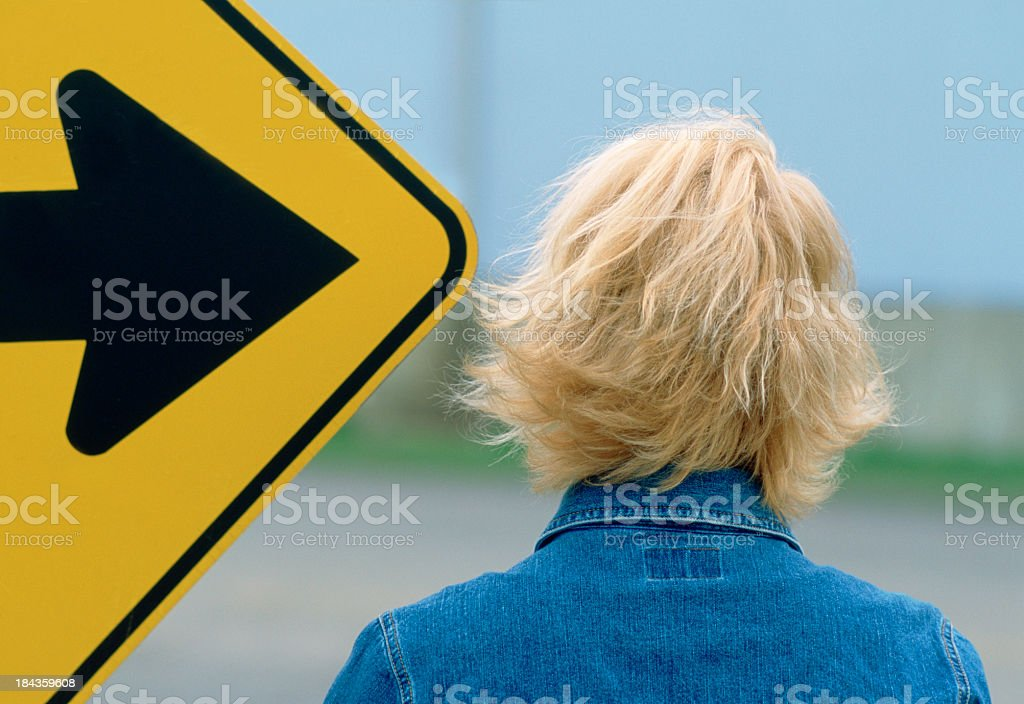 Woman with road sign pointing to head. royalty-free stock photo