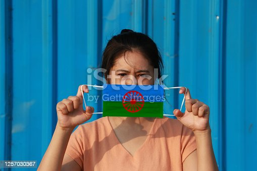 A woman with Romani people flag on hygienic mask in her hand and lifted up the front face on blue background. Tiny Particle or virus corona or Covid 19 protection. Concept of Combating illness.