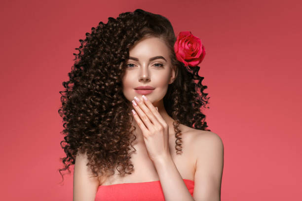 Woman with rose flower. Beauty female portrait with beautiful rose flower and salon hairstyle over pink manicure nails  background. stock photo