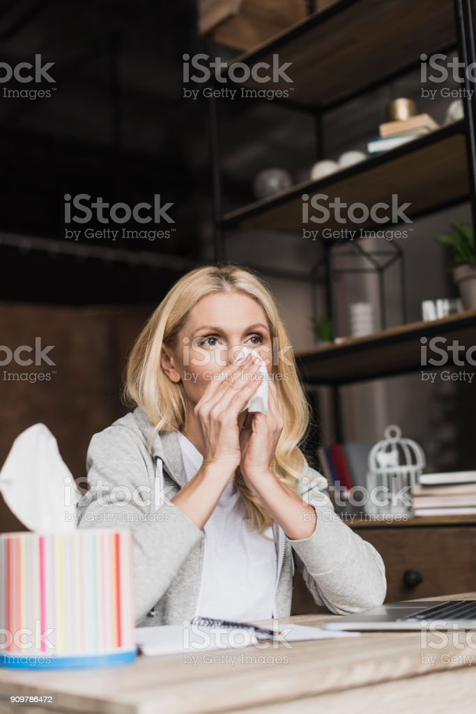woman with runny nose holding paper towel stock photo