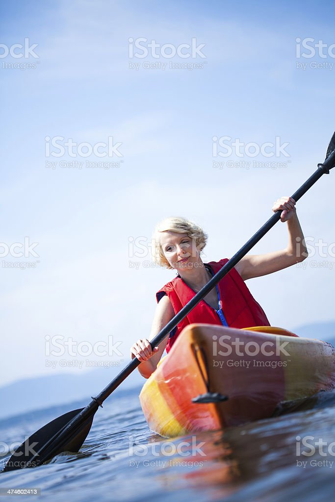Woman With Safety Vest Kayaking Alone on a Calm Sea stock photo