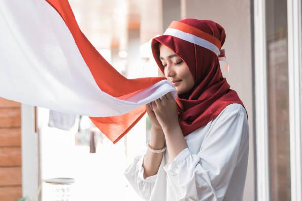 mulher com lenço beijando a bandeira da indonésia - bandeira da indonesia - fotografias e filmes do acervo