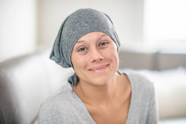 Woman with scarf A beautiful woman with cancer sits in her hospital bed at home. She is looking into the camera in this portrait. cancer cell stock pictures, royalty-free photos & images