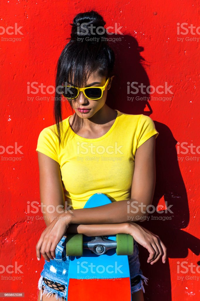 Woman with scateboard looking down - Royalty-free 25-29 Years Stock Photo