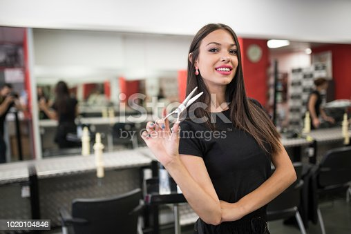 istock Woman with scissors posing in barber shop 1020104846