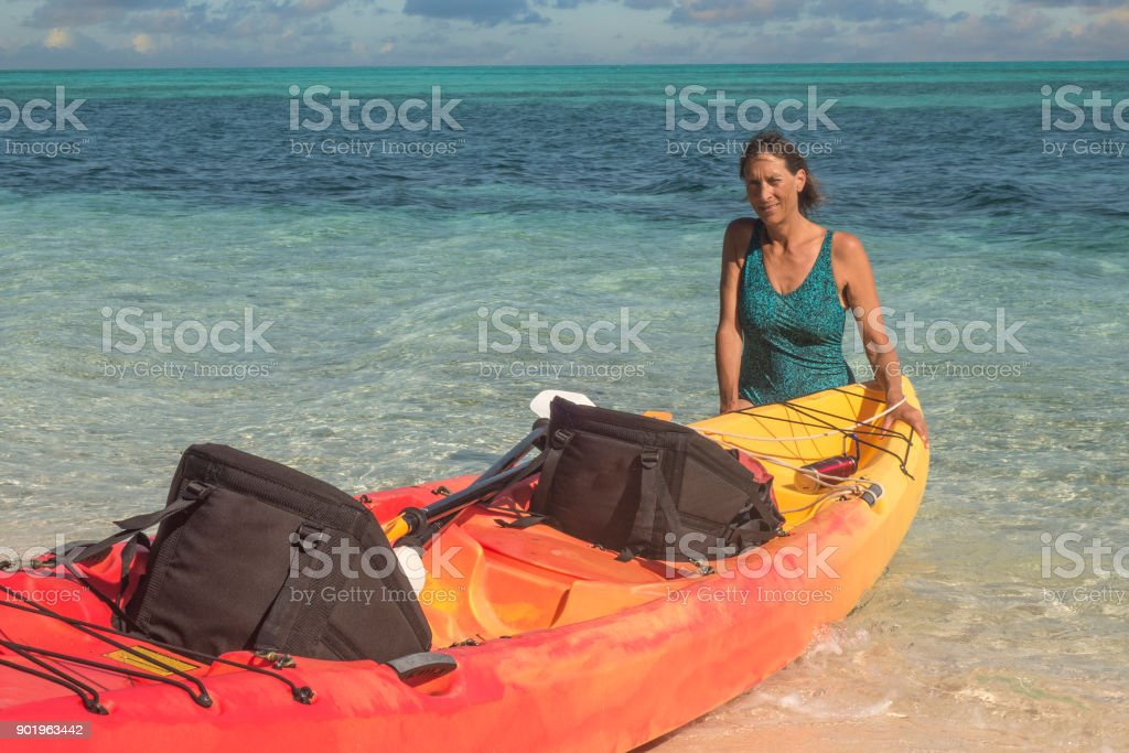 Woman with sea kayak on atoll stock photo