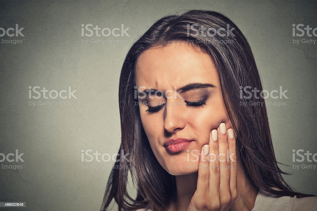 woman with sensitive toothache crown problem Closeup portrait young woman with sensitive toothache crown problem about to cry from pain touching red area outside mouth with hand isolated gray background. Negative emotion face expression feeling Wisdom Stock Photo