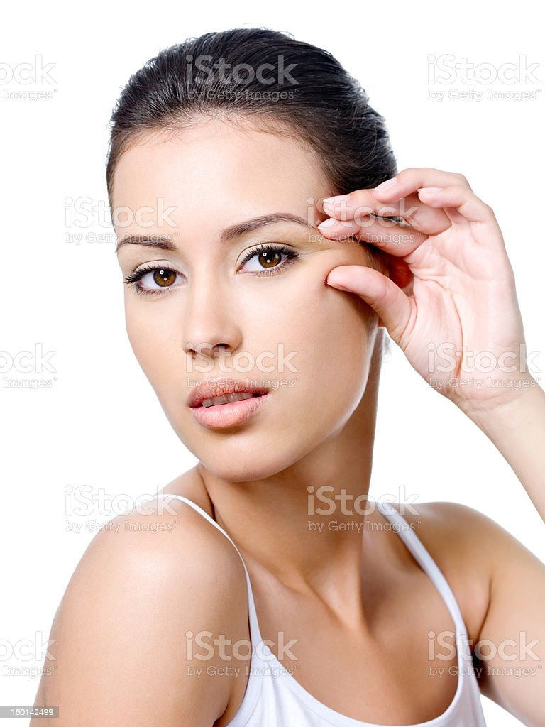 Woman with sensual look pinching skin near the eye stock photo