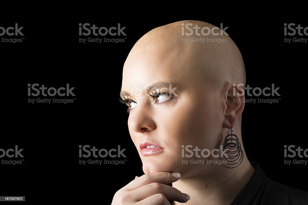 Woman with shaved head in semi-profile, looking to side. royalty-free stock photo