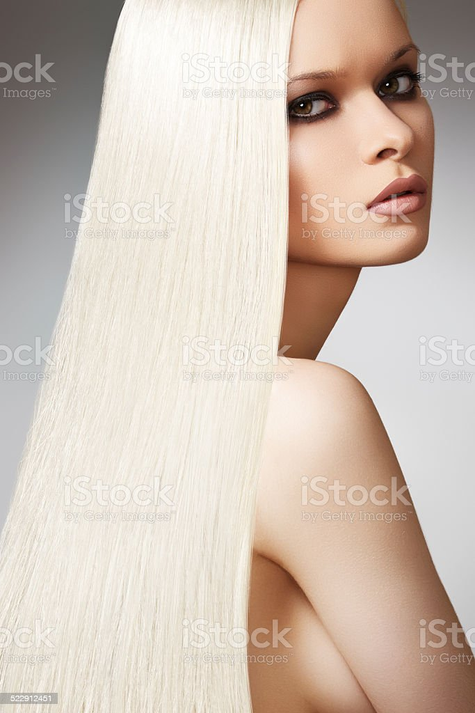 Woman with shiny straight long blond hair and chic make-up stock photo