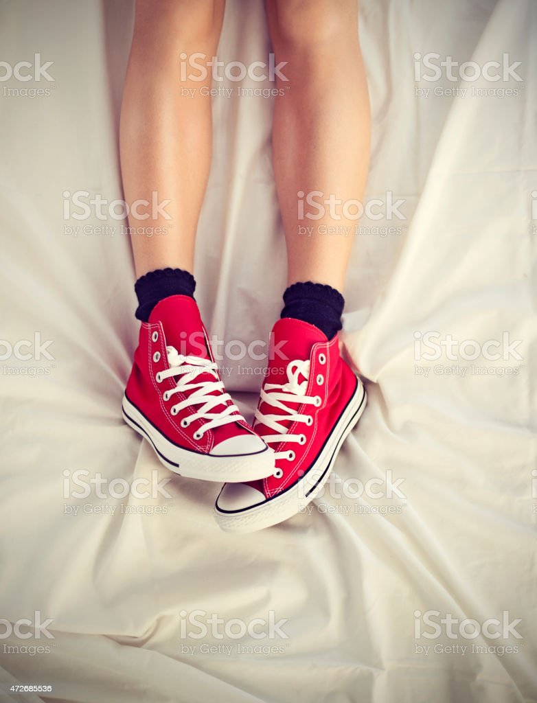 Woman with shoes on bed stock photo