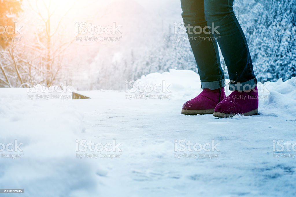 Woman with shoes on snow. stock photo