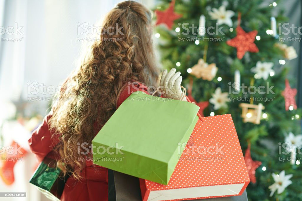 Woman With Shopping Bags And Christmas Gift Near Christmas Tree