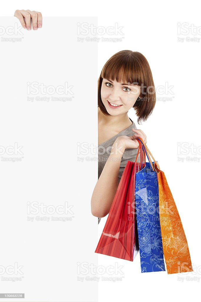 Woman with shopping bags holding blank billboard royalty-free stock photo