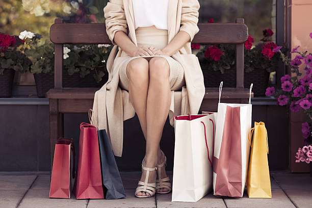 woman with shopping bags sitting on bench. - sitzbank schuhe stock-fotos und bilder