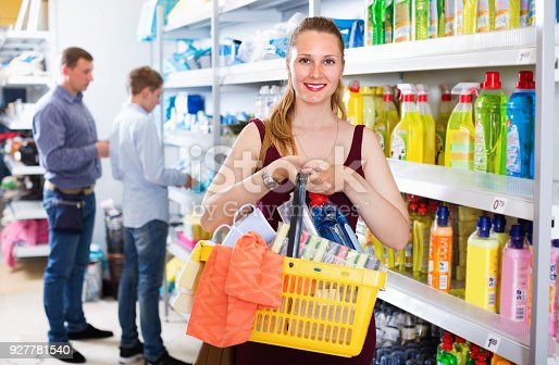 istock Woman with shopping basket choosing detergent 927781540