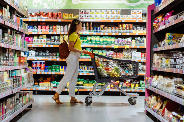 woman with shopping between store shelf copy space woman with shopping between store shelf copy space aisle stock pictures, royalty-free photos & images