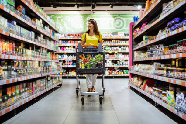 woman with shopping between store shelf portrait copy space woman with shopping between store shelf portrait copy space buying stock pictures, royalty-free photos & images